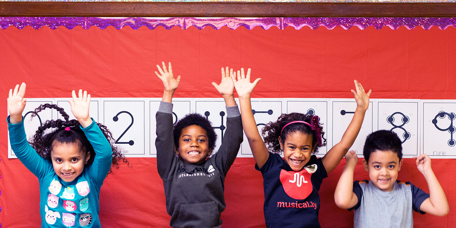 Smiling students with hands raised in front of bulletin board.